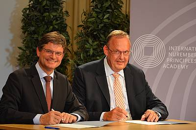 Prof. Joachim Hornegger, President of Friedrich-Alexander-Universität Erlangen-Nürnberg (left), and Klaus Rackwitz, Director of the Nuremberg Academy (right), signing the cooperation agreement