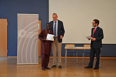 Mr. Klaus Rackwitz, Director of the Nuremberg Academy presents the certificate of participation.